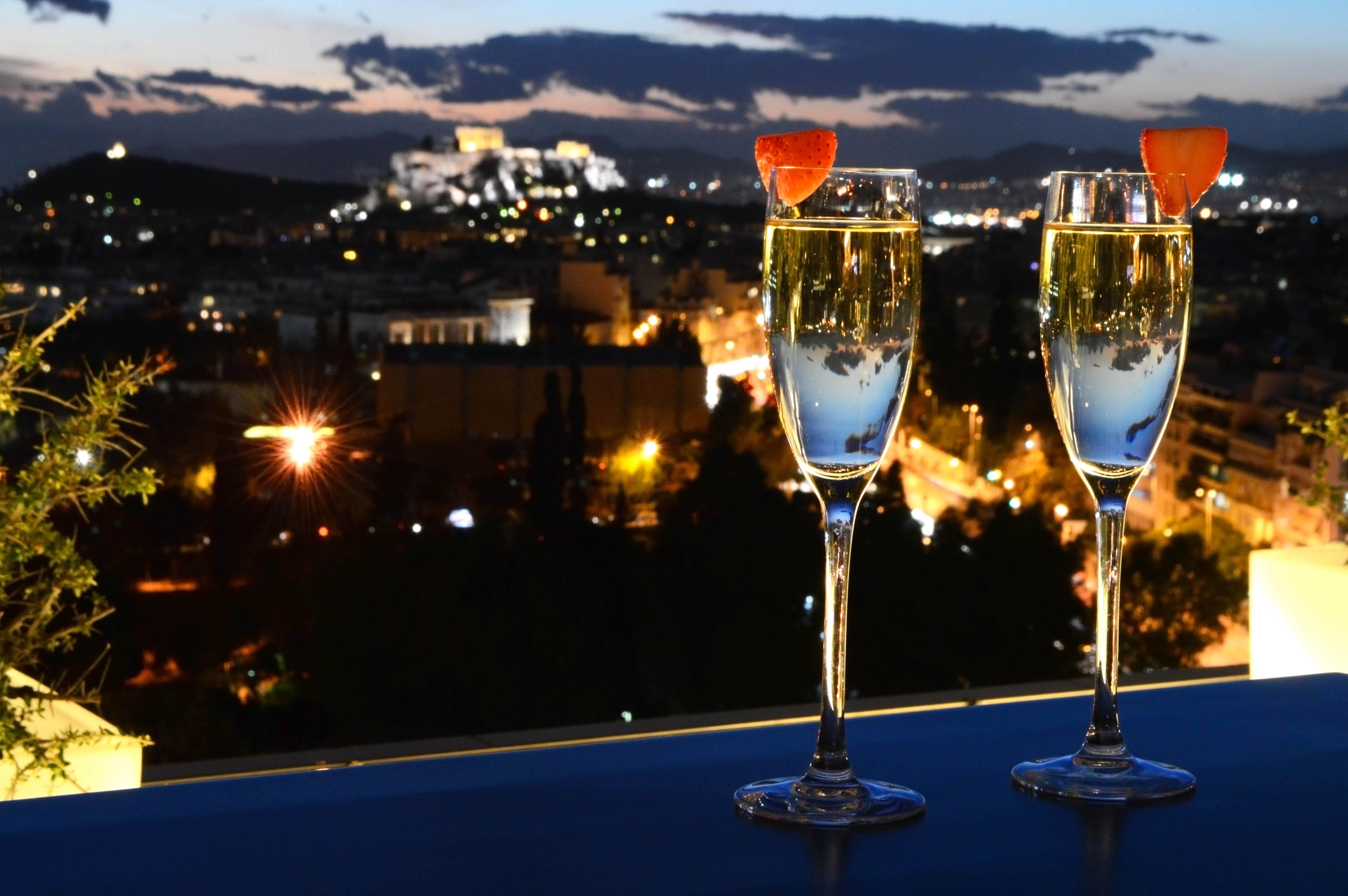 Copas de champagne en la terraza con vistas a la Acrópolis del Galaxy Bar del hotel Hilton de Atenas