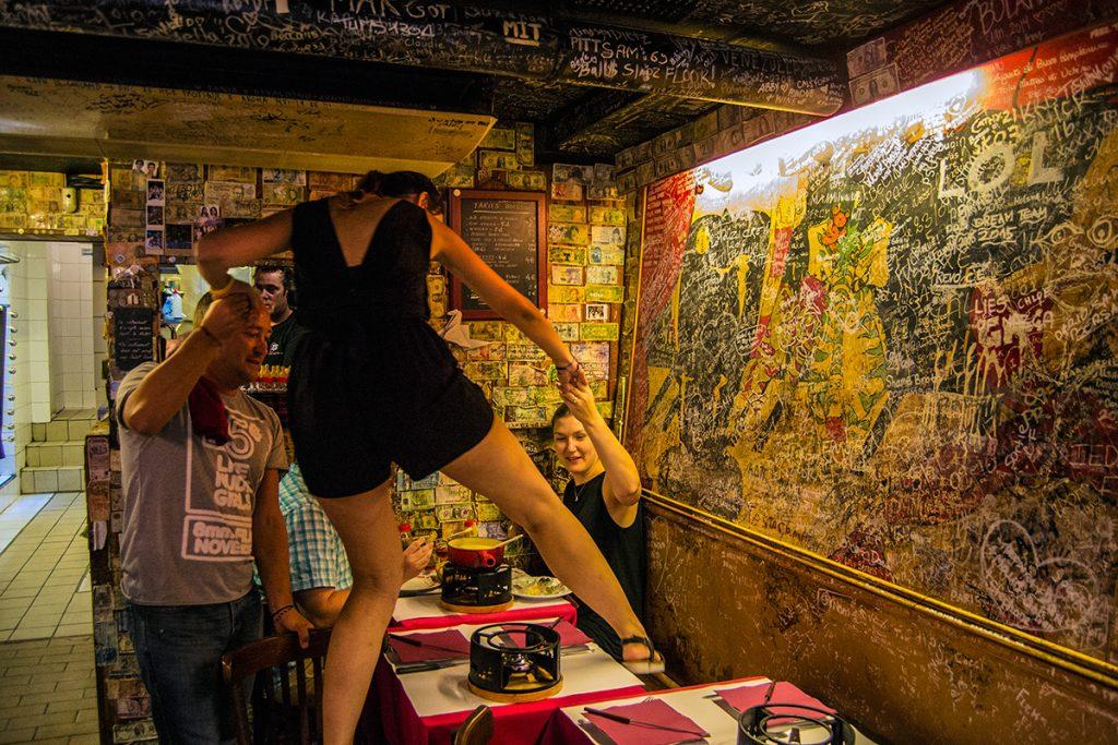 Manera de sentarse en una mesa en el Refuge des Fondus - Qué ver en Montmartre