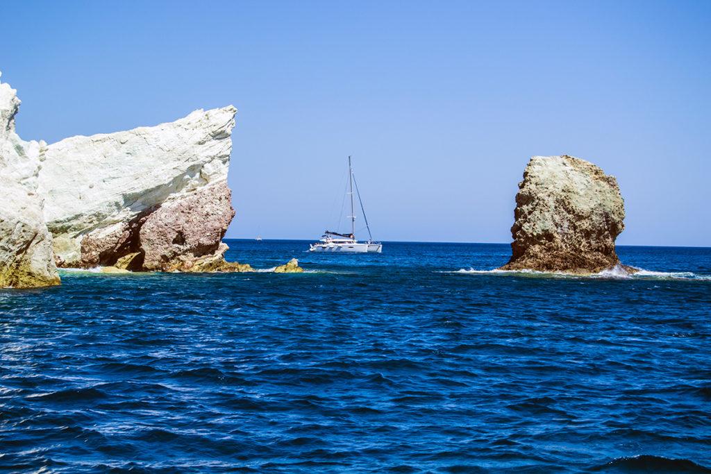 Barco entre grandes rocas de la playa blanca de Santorini - Descubrir Santorini