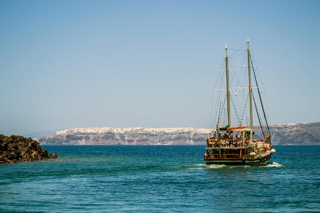 Barco y vistas del pueblo de Oia - Descubrir Santorini