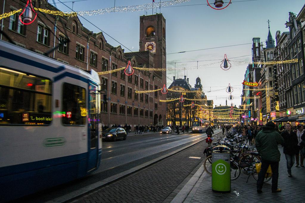 Calle Damrak iluminada con luces navideñas - Disfrutar Amsterdam